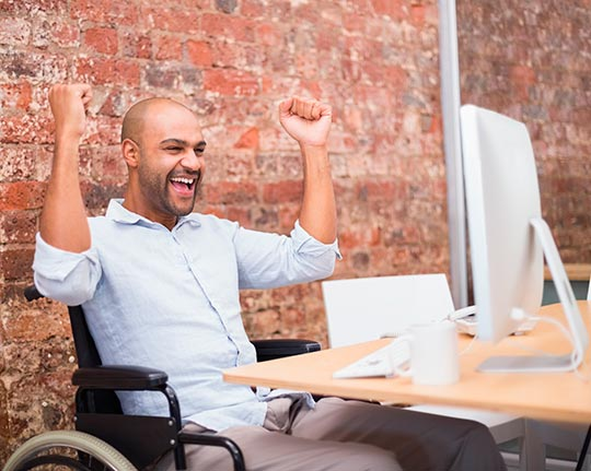 Happy man in wheelchair with a computer