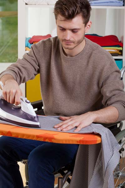 young man ironing clothes in a wheelchair